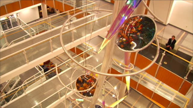 colorful circles of blown glass decorate a spiral staircase. - spiral staircase stock videos & royalty-free footage