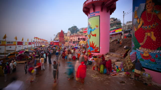 Colorful clothes and colorful street scene on busy riverbank in India during Kumbh Mela