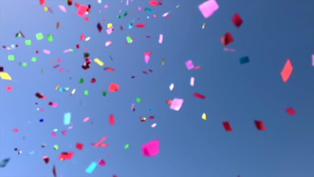colorful confetti flying in slow motion with clear blue sky. - confetti stock videos & royalty-free footage