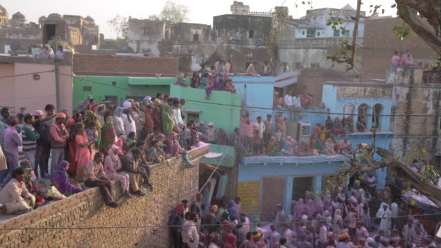 colorful crowd celebrates the holi festival in rural india - uttar pradesh stock videos and b-roll footage