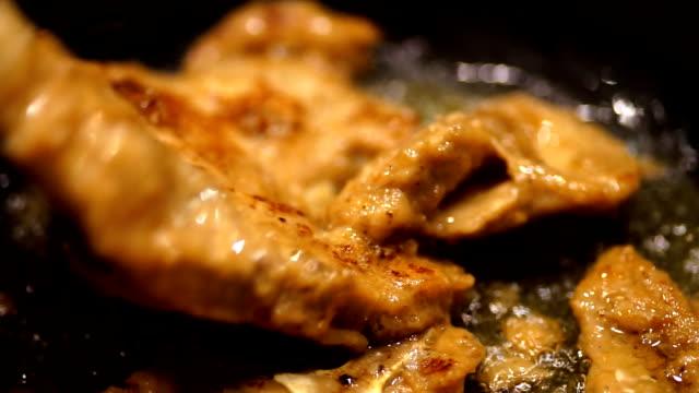 Colorful Cuisine: Juicy pork steaks fried in fraying pan.