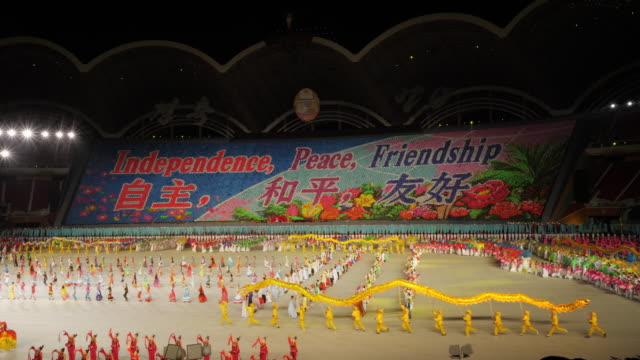 colorful dancers perfoming with a chinese dragon during mass games in pyongyang, north korea, dprk. wide shot - north korea stock videos & royalty-free footage