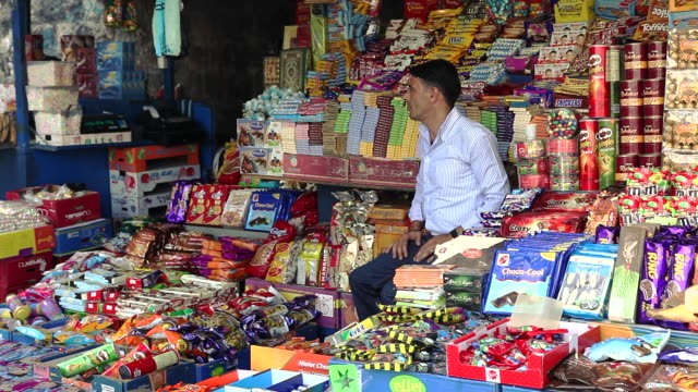 Colorful displays of candy surround a vendor in the Arab market outside of the Old City in East Jerusalem