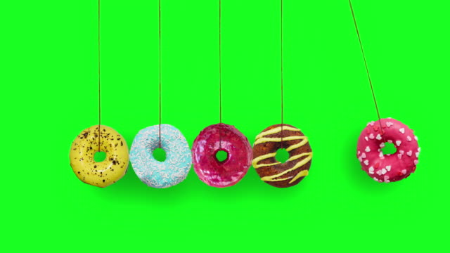 colorful doughnuts swing as a newton's cradle on chroma key background - unhealthy eating stock videos & royalty-free footage