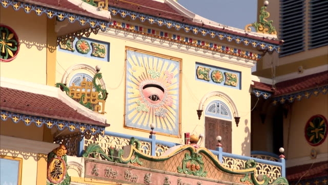 a colorful eye of providence adorns the exterior of the cao dai temple. - tay ninh stock videos & royalty-free footage