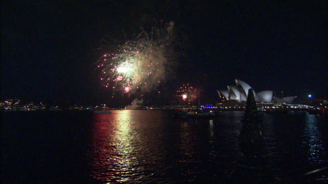 stockvideo's en b-roll-footage met colorful fireworks explode and sparkle over the sydney opera house. - international landmark