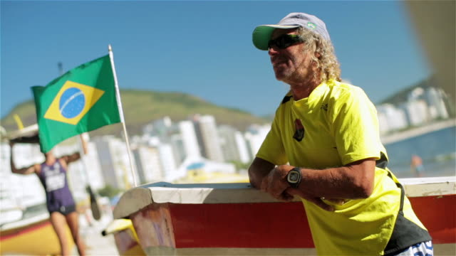 Colorful fisherman leans against boat on beach with Brazilian flag waving as man with paddleboard walks by