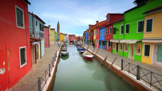 colorful fisherman's homes dot either side of a canal  in the village of burano in venice, italy - mediterranean culture stock videos & royalty-free footage
