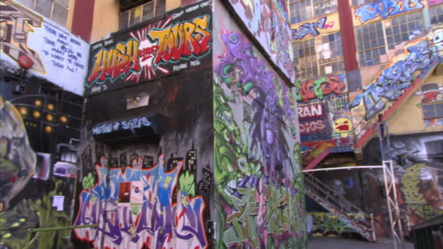 Colorful graffiti murals cover a fire escape, a dumpster and alley walls in Queens.