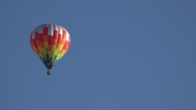 a colorful hot air balloon moves in the blue sky - 熱気球点の映像素材/bロール