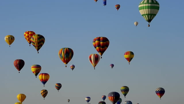 colorful hot air balloons dot the blue sky at the albuquerque balloon fiesta. - hot air balloon stock videos & royalty-free footage