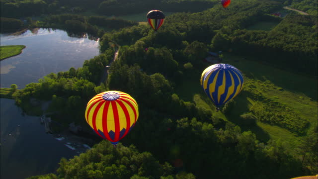 colorful hot air balloons drift above trees and water. - vermont stock videos & royalty-free footage
