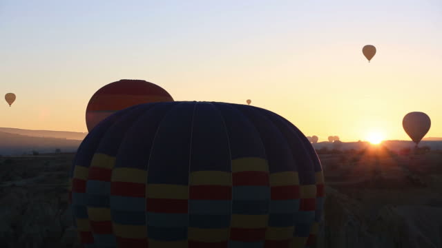 Colorful hot air balloons flying over valleys