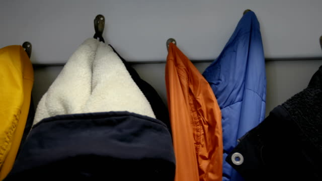 colorful jackets on coat rack - rack stock videos & royalty-free footage
