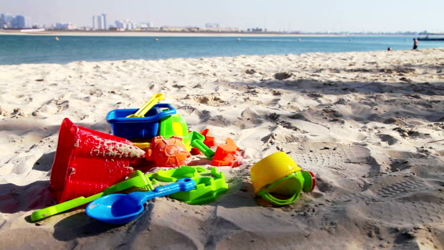Colorful kids toys on sand beach