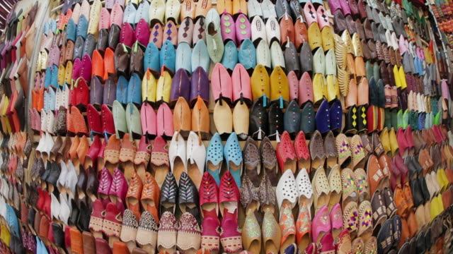 colorful leather slippers cover the wall of a market stall. - market stall stock videos and b-roll footage