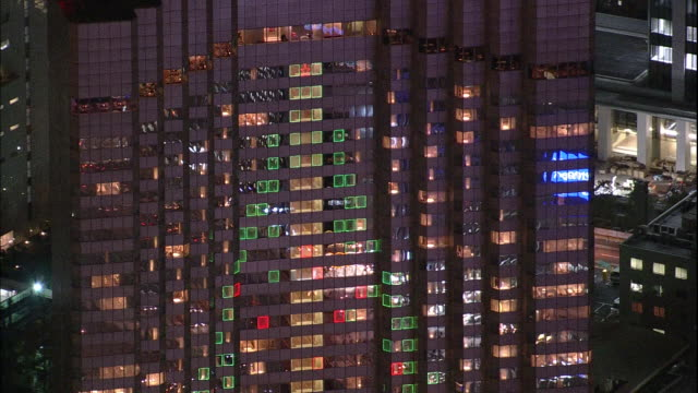 colorful lights depict a christmas tree shape on a skyscraper in tokyo, japan. - viewpoint stock videos and b-roll footage