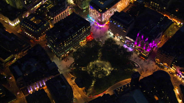 Colorful lights shine around Leicester Square in London's West End at night.