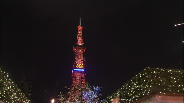colorful lights twinkle on a tv tower and an illuminated light sculpture during the sapporo white illumination in japan. - テレビ塔点の映像素材/bロール