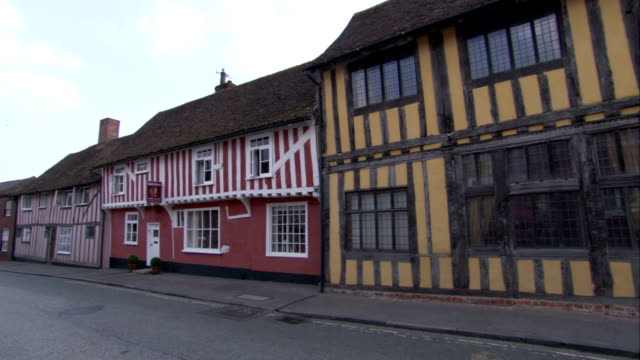 colorful medieval cottages line a street in lavenham. available in hd. - lavenham stock-videos und b-roll-filmmaterial