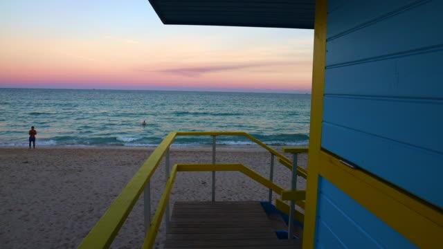 colorful miami beach lifeguard tower with stunning sunset sky and empty beach. - アールデコ地区点の映像素材/bロール