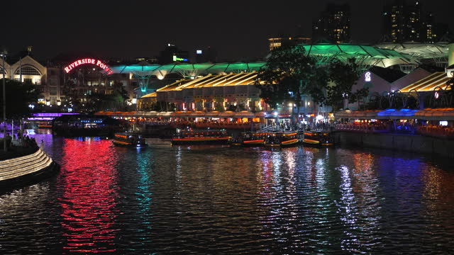 colorful night scene of river with busy tour boats on clarke quay jetty, singapore - singapore river stock videos & royalty-free footage