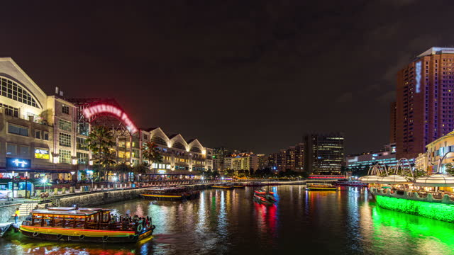 colorful night scene of river with busy tour boats on clarke quay jetty, singapore, time lapse video - singapore river stock videos & royalty-free footage
