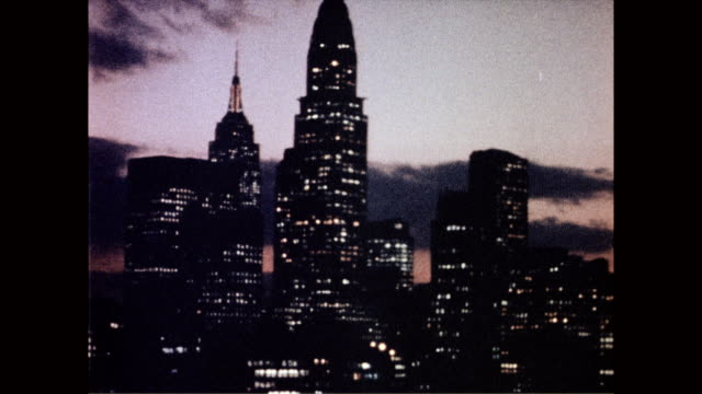 colorful night sky as back drop to silhouetted cityscape / manhattan sky scrapers full of lighted windows / headlights of cars stand out against the... - 1958年点の映像素材/bロール