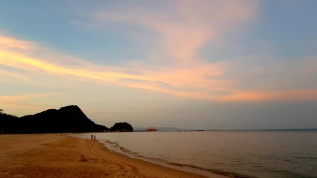 vídeos de stock e filmes b-roll de colorful ocean beach sunrise with deep blue sky and sun rays - invertebrado