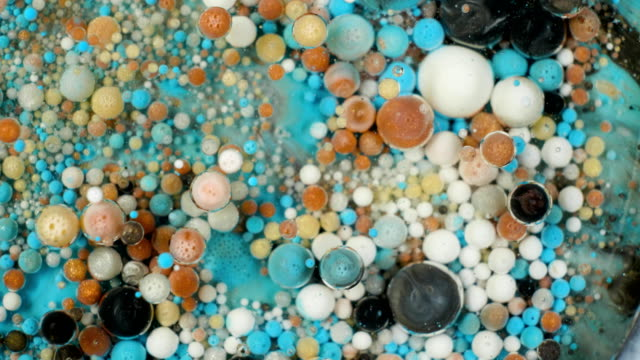 Colorful paint in bubbles organically moves in the liquid