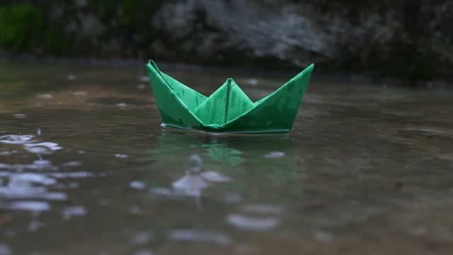 vidéos et rushes de bateau en papier coloré flottant sur l'eau - origami