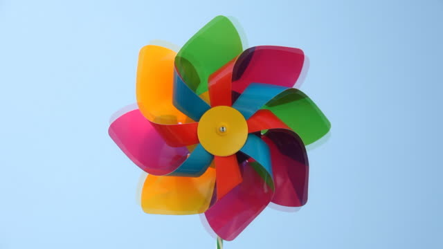 carta colorato, mulino a vento filatura in blu cielo - girandola video stock e b–roll