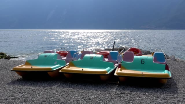 stockvideo's en b-roll-footage met colorful pedal boats on lake shore, limone sul garda, lake garda, lombardy, italy - waterfiets