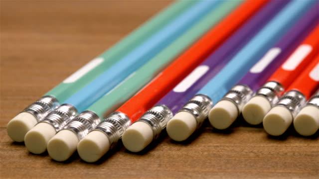 vídeos de stock e filmes b-roll de colorful pencils with erasers on brown wooden table - borracha material de escritório