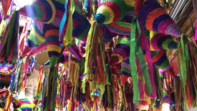 vídeos de stock, filmes e b-roll de colorful pinatas hang on a market stall in the picturesque coyoacan neighborhood as the holiday season approaches on december 12, 2020 in mexico... - papier