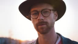 Colorful portrait of young stylish guy with red beard in glasses and in hat looking at camera during sunset outdoors. Cinematic shot