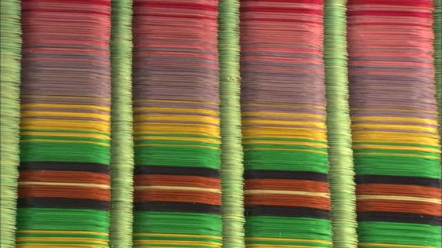Colorful reeds comprise a mat.
