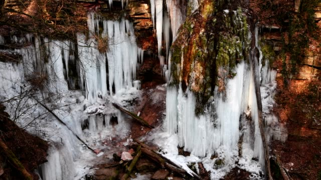 Colorful sandstone canyon in winter with icicles on mossy tuff rock with flying film drone, Klingelsbach-Schlucht, Triefenstein, Bavaria, Germany