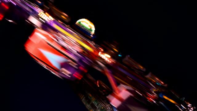 bunte spinnrad im vergnügungspark in der nacht - zentrifuge stock-videos und b-roll-filmmaterial