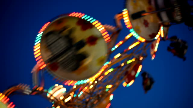 vídeos de stock e filmes b-roll de colorful spinning wheel in amusement park at night - correia transportadora