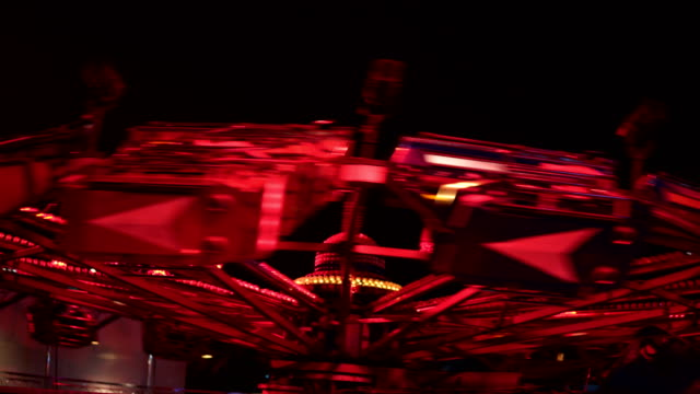 colorful spinning wheel in amusement park at night - girandola video stock e b–roll