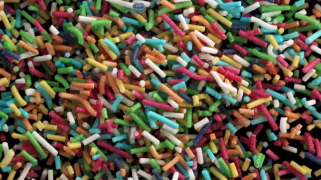 vídeos de stock, filmes e b-roll de confete de açúcar colorido no ar - sprinkles