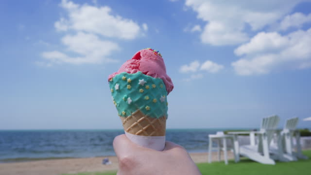 colorful summer ice cream cone on hand with blue sky beach sea background - ice cream cone stock videos & royalty-free footage