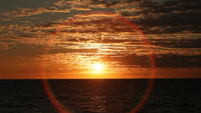 colorful sunset overlooking the ocean as a sail boat is off in the distance. - sundog stock videos & royalty-free footage