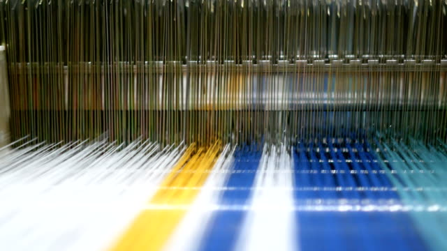 colorful threads on a loom in  weaving loom machine in textile factory - textile industry stock videos & royalty-free footage