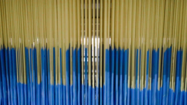 colorful threads on a loom in  weaving loom machine in textile factory - needle plant part stock videos & royalty-free footage