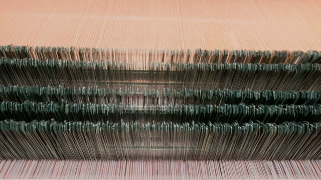 Kleurrijke draden op een weefgetouw in het weven van de machine