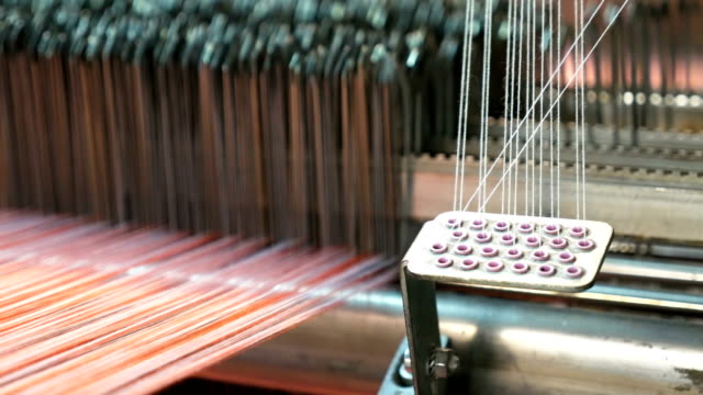 vídeos de stock e filmes b-roll de colorful threads on a loom in weaving machine - textile