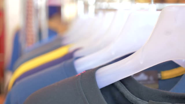 colorful t-shirts on a coat rack,motion focus concept - t shirt stock videos and b-roll footage