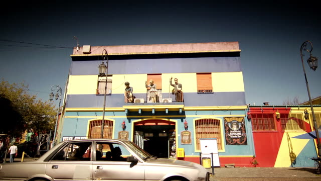 colorful two-story building, paper mache statues of singer carlos gardel, political leader eva peron, soccer player diego maradona on balcony, car... - buenos aires video stock e b–roll